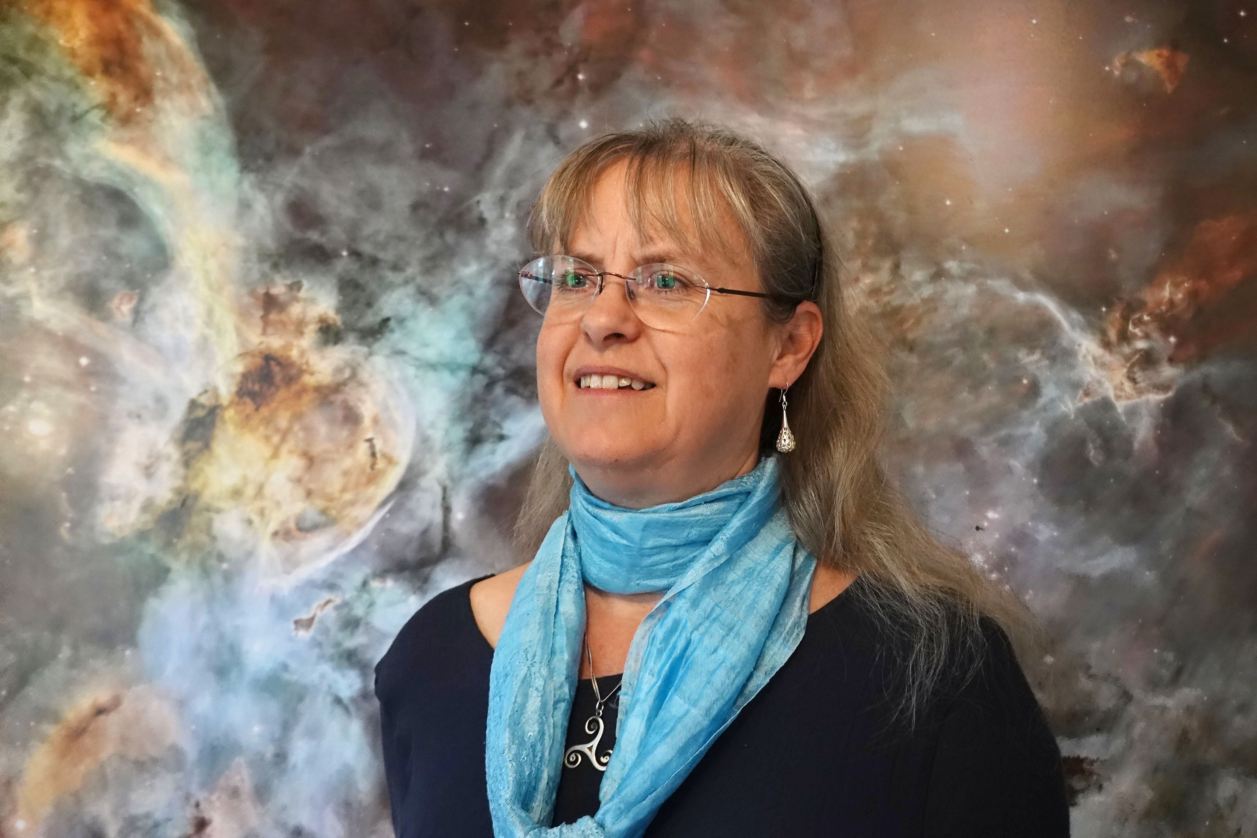 Sylvia Ekström in front of a picture of nebula and stars