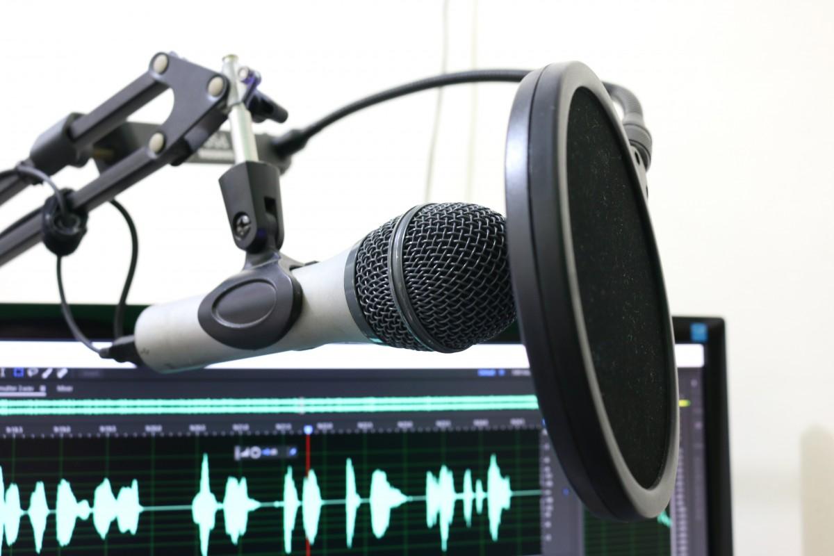 Un microphone devant un écran avec un audiogramme affiché.